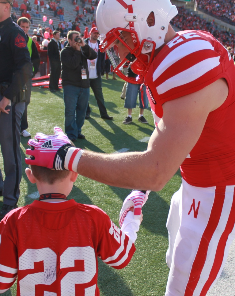 football player greeting kid